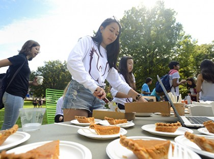A student dishes out slices of pumpkin pie