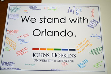 a poster reading 'We stand with Orlando' signed in rainbow-colored pens