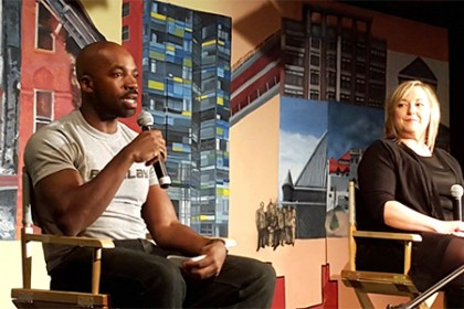 Presenters seated on stage with colorful mural backdrop