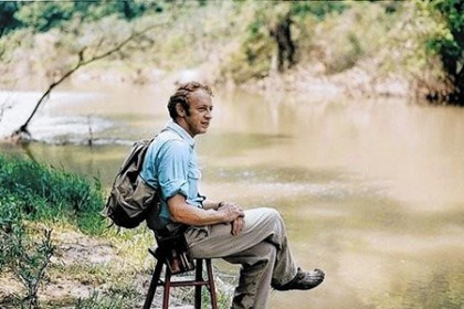 Reds Wolman sits on a stool beside a river