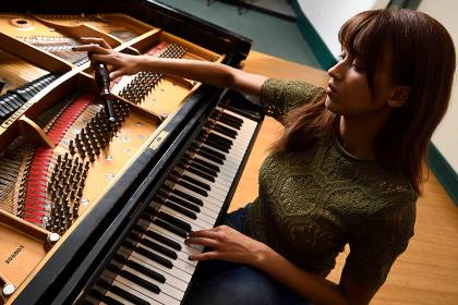 """Renee Kelsey adjusts a tuning pin on the """"nameless"""" piano in the Cohen-Davidson Family Theatre."""