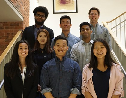Eight students stand on a staircase