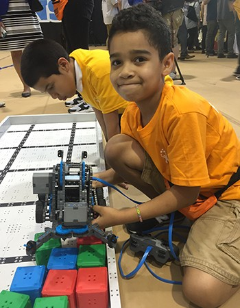 A boy in a yellow shirt holds a small robot with gears and metal parts, which scoops colored plastic blocks