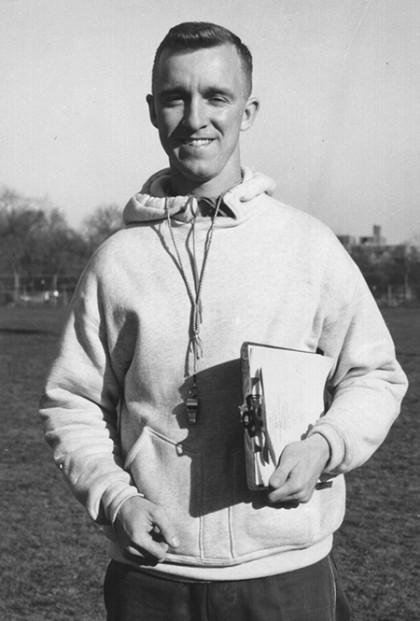Black and white photo of Bob Scott in hooded sweatshirt holding a clipboard