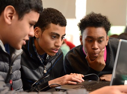 3 young men work together at a laptop computer