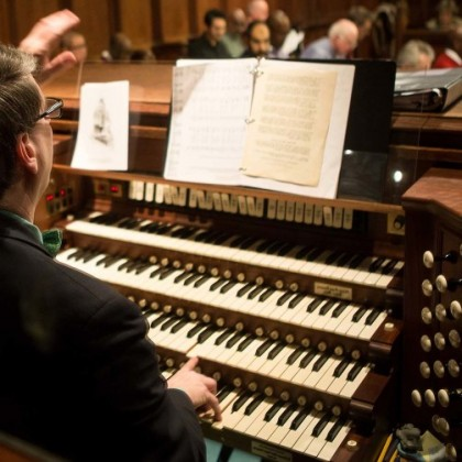 An organist plays on a four-tiered organ