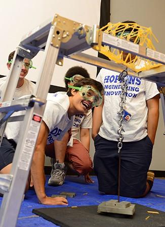 Team members watch from below as their spaghetti bridge breaks