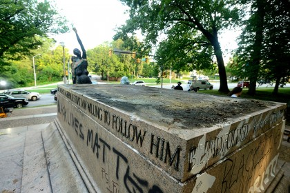 An empty statue plinth is vandalized with graffiti