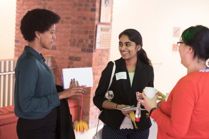 Three young women talk during break in symposium
