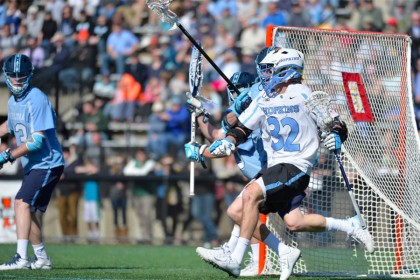 JHU lacrosse player drives towards the net