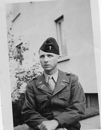 A black and white photograph shows a young man in a military uniform and beret