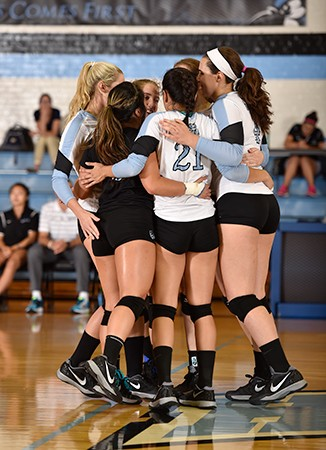 JHU players huddle on the court following a point