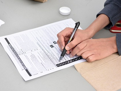 Image of student's hands as she fills out Maryland voter registration form