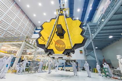 Technicians use a crane to lift the James Webb Space Telescope inside a clean room at NASA's Goddard Space Flight Center in Greenbelt, Maryland