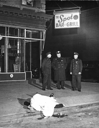 A group of police officers stand beside a dead body at a diner
