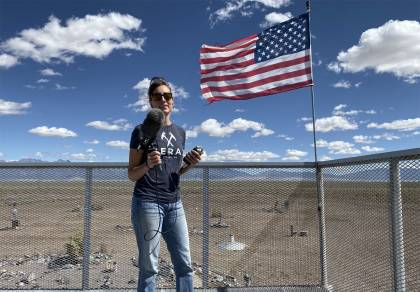 Laura Krantz holding a mic in front of an American flag