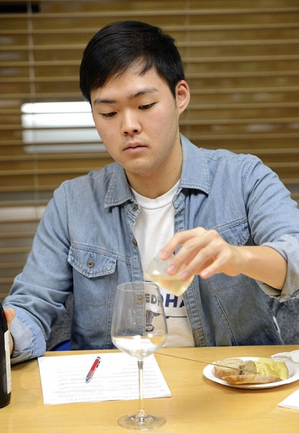 Student pouring wine sample into glass