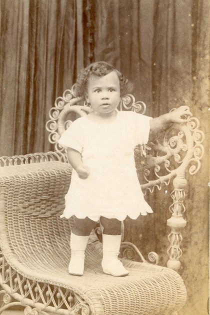 Sepia photo of small child standing on a chair. She wears a dress and boots.