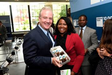 Sen. Chris Van Hollen with a box of berries and LaQuicha Brown