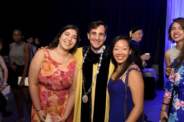 President Daniels poses or a photo with two female students