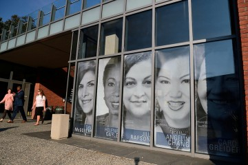 Window panels of the Mattin Center feature black and white clings of women's portraits