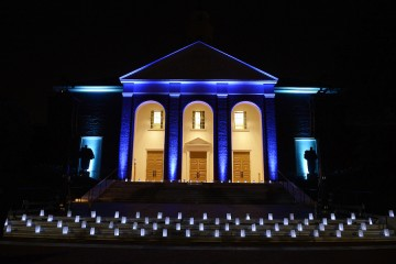 Front of Shriver Hall is illuminated in blue with luminaries on the steps