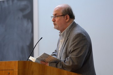 Salman Rushdie, dressed in a gray suit and striped shirt, holds open a hard cover copy of his book, The Golden House, and speaks into a podium microphone