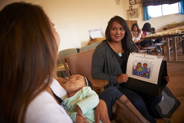 A woman holds a flashcard from a spiral bound notebook depicting a mother feeding a child, while in the foreground, a woman holds her sleeping baby