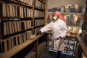A woman in a lab coat and face mask dusts book shelves