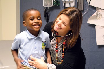A little boy smiles while he is tickled by his doctor, who has a stethoscope in her ears