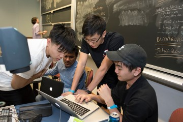 Four students huddle over a laptop