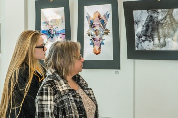 Two people look at photos mounted on the wall