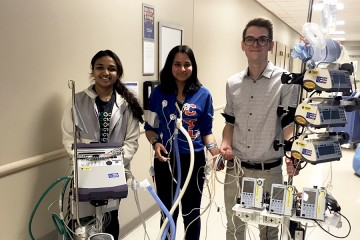 Three students demonstrate a walker built to help ICU patients