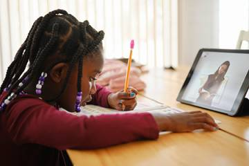 A child does classwork while sitting in front of a tablet displaying a video conference call