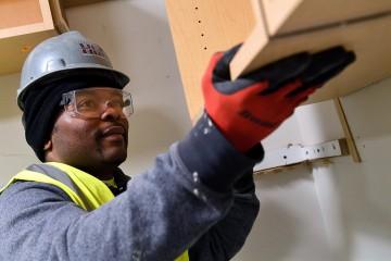 Isaiah Segar installs cabinets
