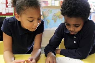 Two children collaborate on a project