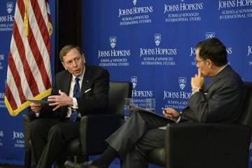 Petraeus gestures and looks at Nasr, who listens with a hand on his chin