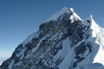 Climbers climb a mountain ridge over Everest