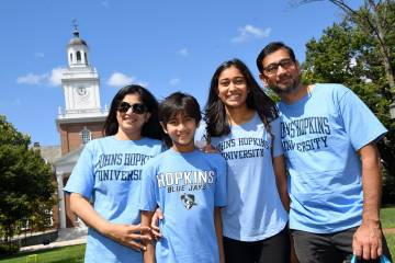 A smiling family of four people wearing blue Johns Hopkins t-shirts