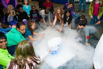 Girls gather around dry ice and fog at APL's Girl Power Event
