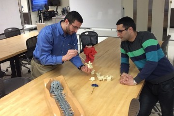 Gulotti (left) holds and examines a model of a vertebral bone while Manbachi observes.