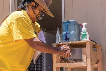 A resident of the Black Rock community of the Navajo Nation uses a hand-washing station provided by the Center for American Indian Health.