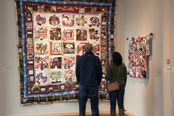 A couple looks at a quilt display