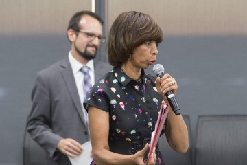 A woman holds a microphone and speaks while a man smiles behind her