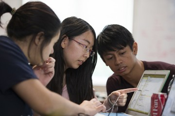 Students work together on a computer