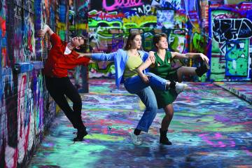 Dancers in a colorful graffitied room