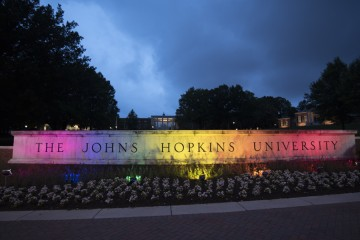 The concrete gateway reading 'The Johns Hopkins University' is lit up with red, orange, yellow, green, blue, and purple lights