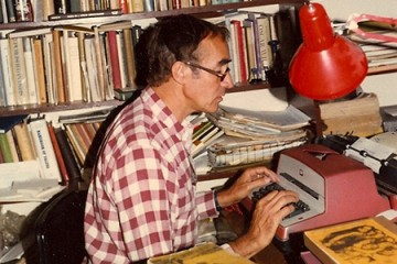 A man with glasses sits at a typewriter in a room with full bookshelves lining the walls