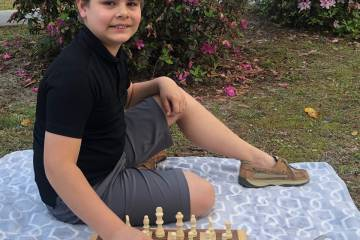 A boy plays chess outdoors