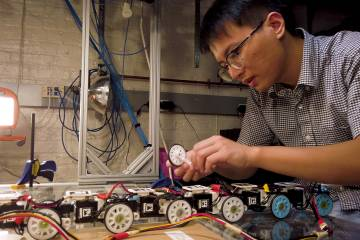 An engineer works on a snake robot